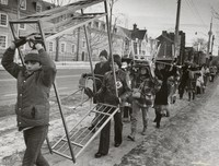 Students, staff and alumni carry pieces of light office furniture two blocks to the new Innis College, 1976